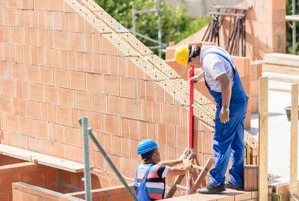 maçons construisant un mur en brique